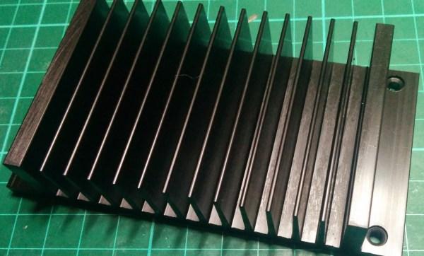 a black aluminum heatsink with fins on a green matt