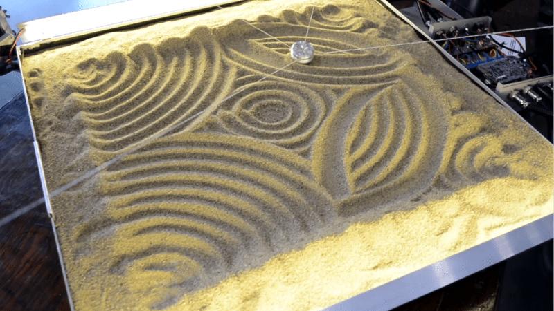 Four strings drag an aluminum slug through a sandbox