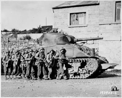 Yanks_of_60th_Infantry_Regiment_advance_into_a_Belgian_town_under_the_protection_of_a_heavy_tank._-_NARA_-_531213