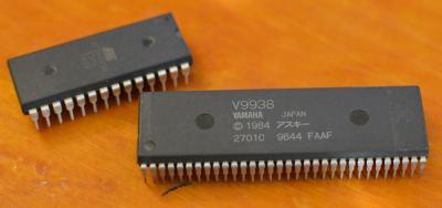 An SDIP-64 chip compared to a DIP-28 chip. Note the finer lead spacing on the SDIP device.