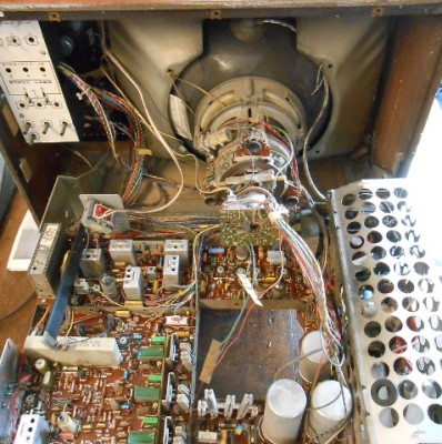 A 1972 ITT CVC5, a TV from the live-chassis era. None of the circuits you see are isolated from the mains. To the left of the big round capacitors bottom-centre is a row of dropper resistors from which lower voltages are derived.