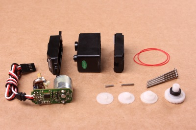 A disassembled servo motor showing the controller, motor, rotary encoder and gears. By oomlout - SERV-05-ST_TEARDOWN_03, CC BY-SA 2.0