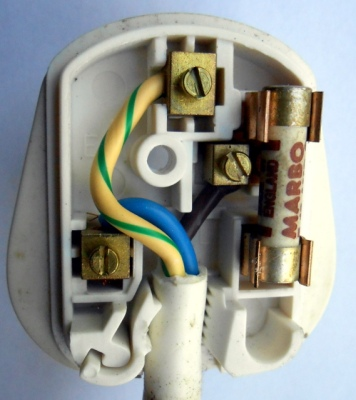 A BS1363 plug with its cover removed. At the top: earth, bottom left: neutral, on the right: 13A fuse and live.