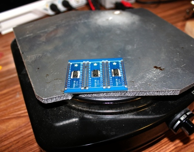 A hot plate with aluminum on top. Some breakout boards are just starting to flow.