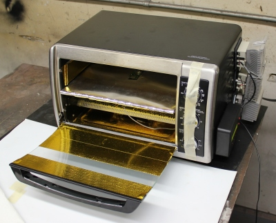 A heavily modified oven with reflect-a-gold for better thermal performance, an extra heating element, Arduino-based PID controller, and solid state relays. This oven was used in production for a few thousand units.