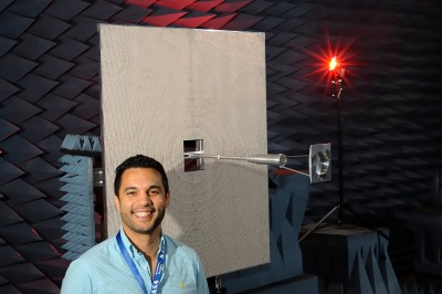 Nacer Chahat poses next to OMERA fixed protoype in one of JPL's anechoic chambers