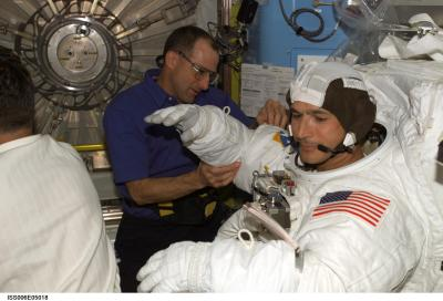 Flight engineer Petit helping MS Herrington don his EMU space suit, Source: NASA