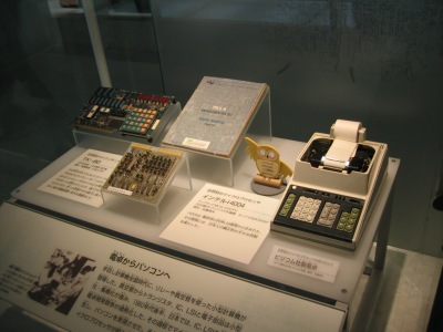 Busicom calculator motherboard based on 4004 (center) and the calculator (right)