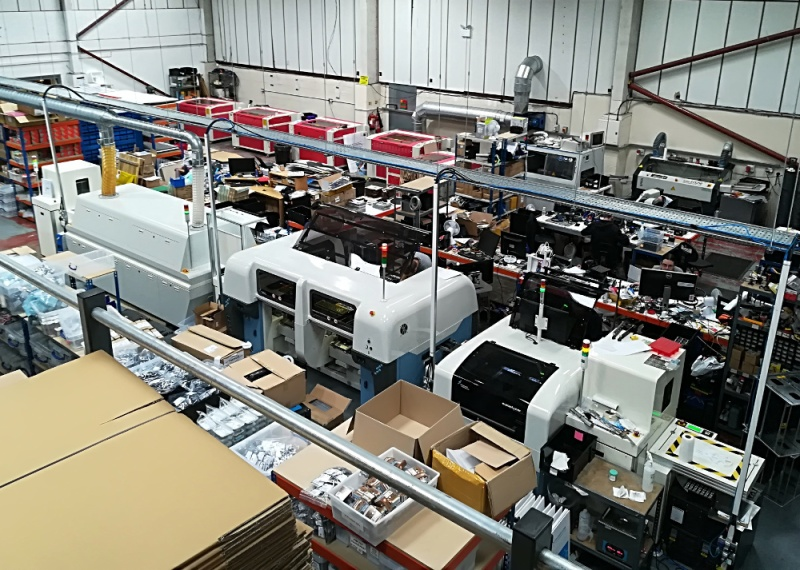 The Pimoroni shop floor. Across the centre is the reflow line, against the back wall are the laser cutters.