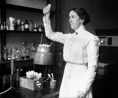 Portrait of Alice Evans in a laboratory, observing a test tube
