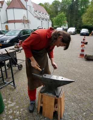 My usual forging attire of steel toecap workboots, spark-resistant overalls, and blacksmith's leather apron. The forge is outside Hack42 hackerspace, Arnhem, and is set up a bit too low for me. Photo: (c) Martina Short, used here with permission.
