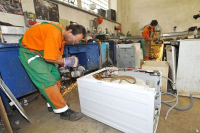Czech waste management workers dismantle scrap washing machines. Tormale [CC BY-SA 3.0].