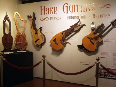 A selection of harp guitars in a museum.
