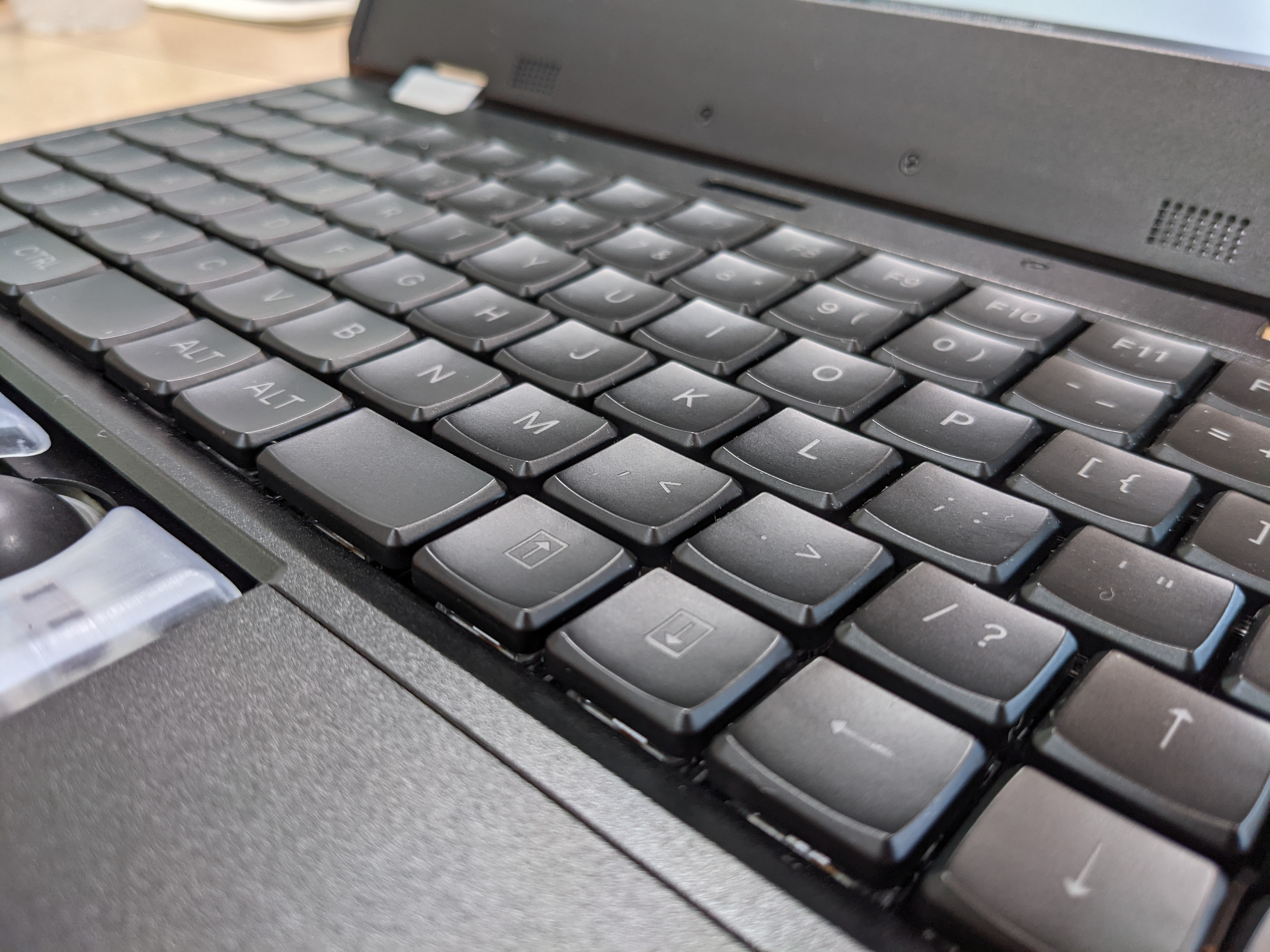 a laptop keyboard with key caps which have a deep depression in the center