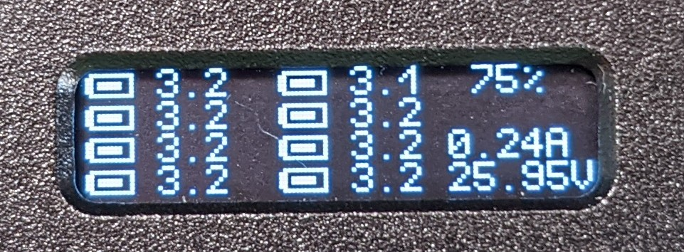 a small OLED display showing battery cell voltages