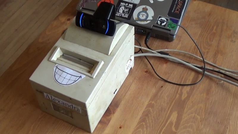 Cobbled together proof-of-concept vaccination verification system, showing a dot-matrix receipt printer, a webcam for QR code scanning, and an old laptop running the software