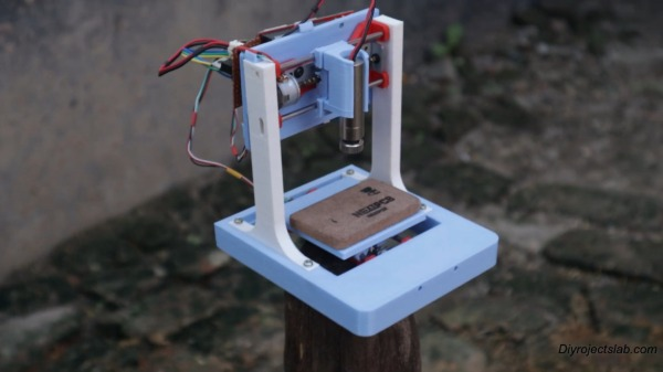 A 3D-printed mini laser engraver made from DVD-RW drive motors.