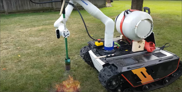 Flamethrower weedkiller mounted on a robot arm riding a tank tracked base