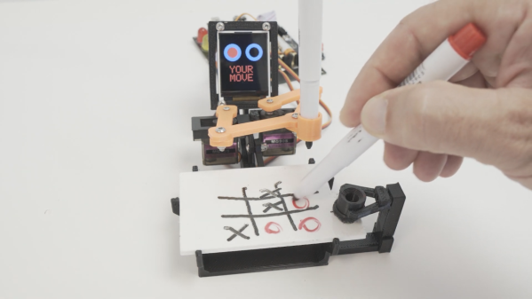 A robot playing tic-tac-toe against a human