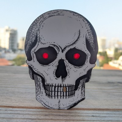 A skull-shaped PCB with two red eyes
