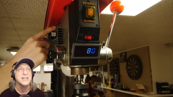 Drill press modded with a treadmill motor, speed controller, lights, and a tachometer.