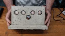 photo of a cast concrete electronics enclosure holding a Nixie tube clock.