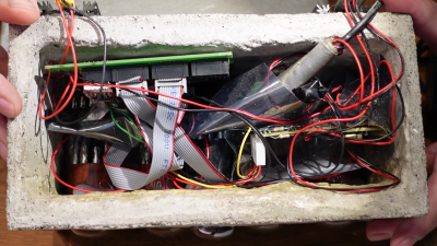 View of the inside of the clock's concrete enclosure, showing a messy array of wires and modules, held together with lots of hot glue and electrical tape.