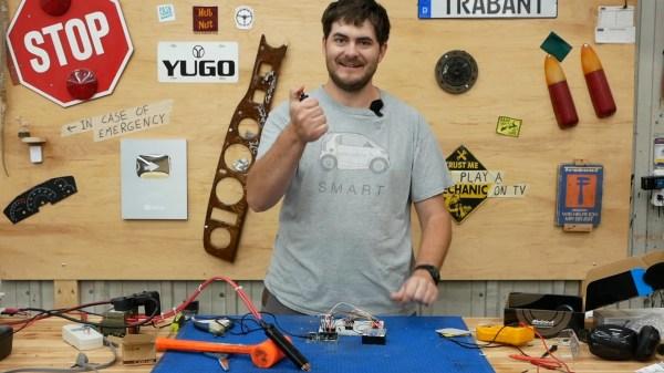 Robert Dunn holds a button in his hand for controlling a spot welder