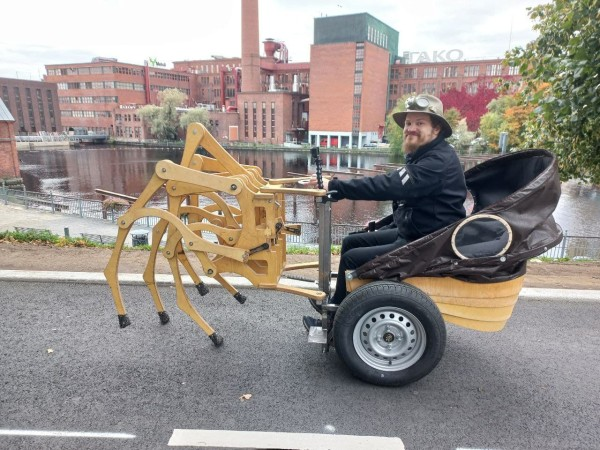 A man riding a buggy pulled by a wooden contraption